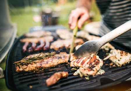 Foto de Unrecognizable man cooking seafood on a barbecue grill in the backyard. Close up. - Imagen libre de derechos