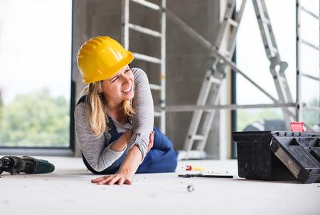 Foto de An accident of a woman worker at the construction site. - Imagen libre de derechos