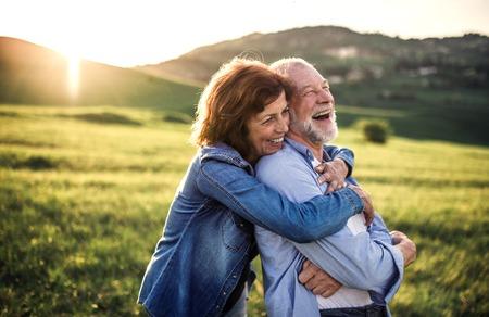 Foto de Side view of senior couple hugging outside in spring nature at sunset. - Imagen libre de derechos