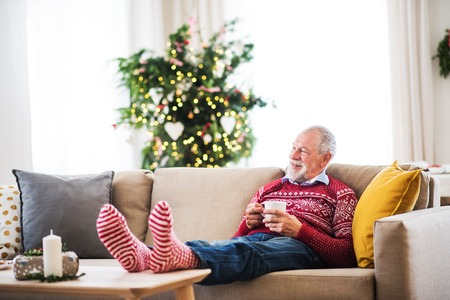 Photo pour A senior man with cup of coffee sitting on a sofa at home at Christmas time. - image libre de droit