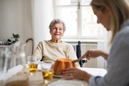 Photo pour A senior woman in wheelchair with a health visitor sitting at the table at home. - image libre de droit