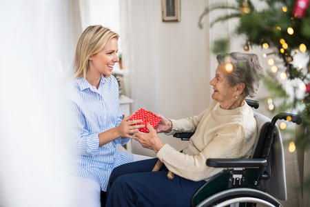 Photo pour Health visitor and senior woman in wheelchair with a present at home at Christmas. - image libre de droit