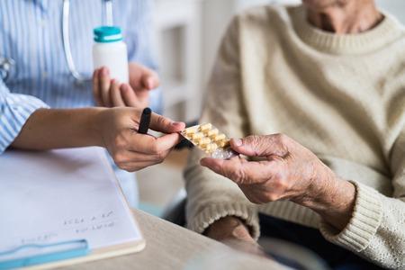 Photo pour An unrecognizable health visitor explaining a senior woman in wheelchair how to take pills. - image libre de droit
