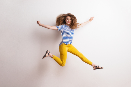Foto de Young beautiful joyful woman with long curly hair in studio, jumping. - Imagen libre de derechos