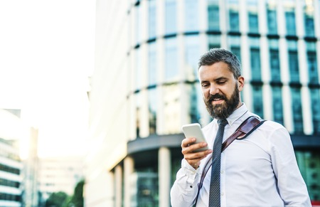 Photo pour A portrait of businessman with smartphone standing on the street in city. - image libre de droit