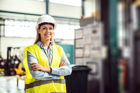 Photo pour A portrait of an industrial woman engineer standing in a factory, arms crossed. - image libre de droit