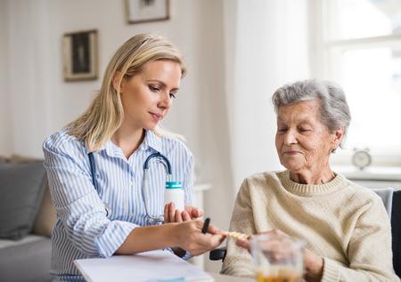 Photo pour A health visitor explaining a senior woman in wheelchair how to take pills. - image libre de droit