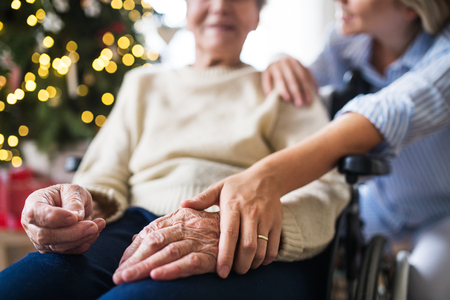 Photo pour A senior woman in wheelchair with a health visitor at home at Christmas time. - image libre de droit