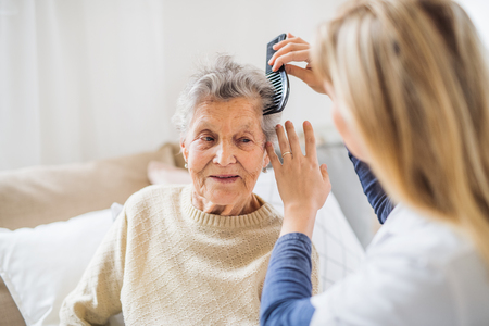 Photo pour A health visitor combing hair of senior woman at home.. - image libre de droit