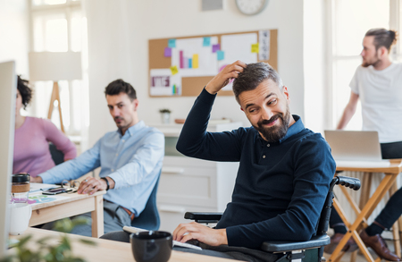 Photo pour Young businessman in wheelchair with colleagues in a modern office. - image libre de droit