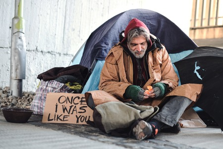 Photo pour Homeless beggar man sitting outdoors in city asking for money donation. - image libre de droit