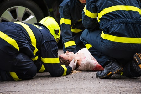 Photo pour Three firefighters helping a young injured woman lying on the road after an accident. - image libre de droit