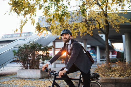 Photo pour Hipster businessman commuter with electric bicycle traveling home from work in city. - image libre de droit