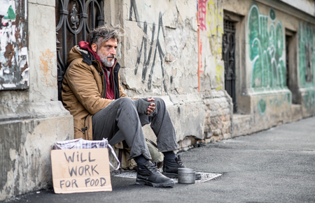 Photo for Homeless beggar man sitting outdoors in city asking for money donation. - Royalty Free Image