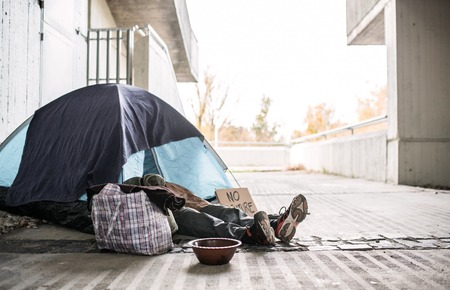 Foto de Legs and feet of homeless beggar man lying on the ground in city, sleeping in tent. - Imagen libre de derechos