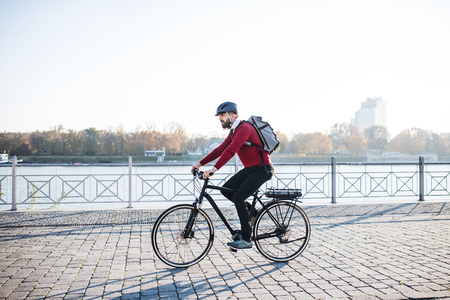 Photo pour Hipster businessman commuter with electric bicycle traveling to work in city. - image libre de droit