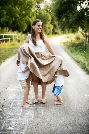 Photo pour Two small sons playing with mother on a road in park on a summer day. - image libre de droit