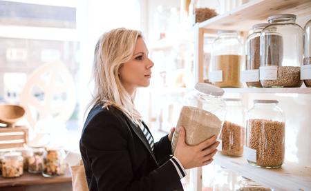 Photo pour A young woman buying groceries in zero waste shop. Copy space. - image libre de droit