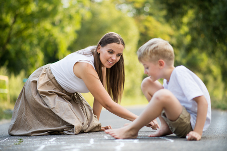 Photo for A small boy with mother drawing hopscotch on a road in park on a summer day. - Royalty Free Image