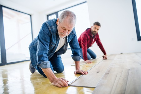Foto de A mature man with his senior father laying vinyl flooring, a new home concept. - Imagen libre de derechos