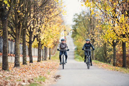 Photo for A senior couple with electrobikes cycling outdoors on a road. - Royalty Free Image
