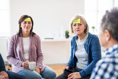 Photo pour Men and women sitting in a circle during group therapy, adhesive notes on forehead. - image libre de droit