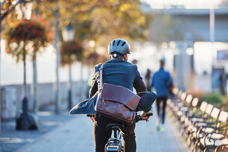 Photo pour A rear view of businessman commuter with electric bicycle traveling to work in city. - image libre de droit