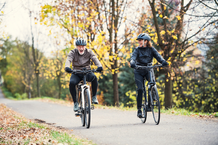 A senior couple with electrobikes cycling outdoors on a road in park in autumn.