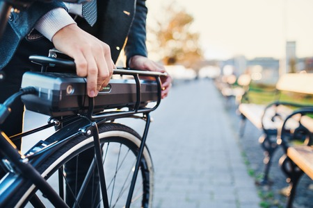 Photo pour A midsection of businessman commuter setting up electric bicycle in city. - image libre de droit