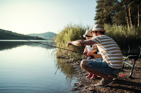 Foto de A mature father with a small toddler son outdoors fishing by a lake. - Imagen libre de derechos