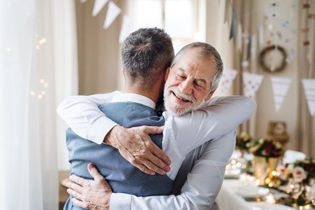 Photo pour A senior and mature man standing indoors in a room set for a party, hugging. - image libre de droit