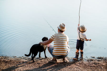 Photo for A rear view of father with a small toddler son and dog outdoors fishing by a lake. - Royalty Free Image