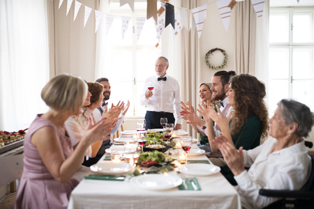 Photo pour A big family sitting at a table on a indoor birthday party, a senior man giving a speech. - image libre de droit