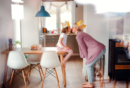 Foto de A portrait of small girl and mother with paper crown at home, kissing. - Imagen libre de derechos