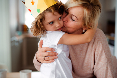 Photo pour A portrait of small girl with grandmother hugging and kissing at home. - image libre de droit