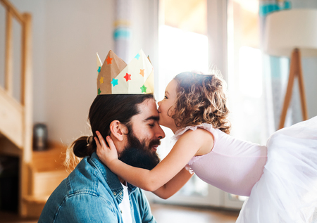Photo pour A side view of small girl with a princess crown and young father at home, playing. - image libre de droit