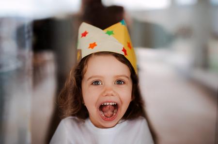 Foto de A small girl with a paper crown at home, looking at camera. - Imagen libre de derechos