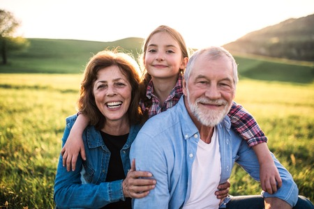 Photo pour Senior couple with granddaughter outside in spring nature, relaxing on the grass. - image libre de droit