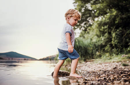 Photo pour A wet, small toddler boy standing outdoors in a river in summer, playing. - image libre de droit