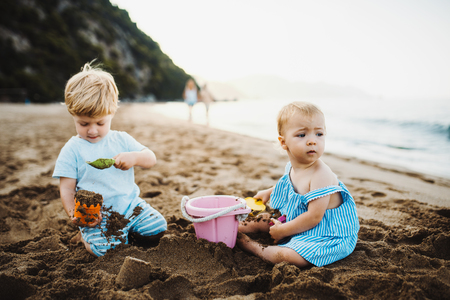 Photo pour Two toddler children playing on sand beach on summer holiday. - image libre de droit