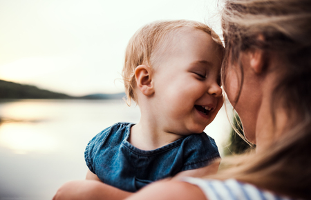 Photo pour A close-up of mother with a toddler daughter outdoors by the river in summer. - image libre de droit