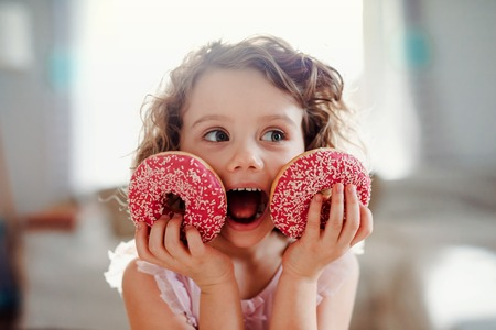 Foto de A small girl with doughnuts at home, looking at camera. - Imagen libre de derechos