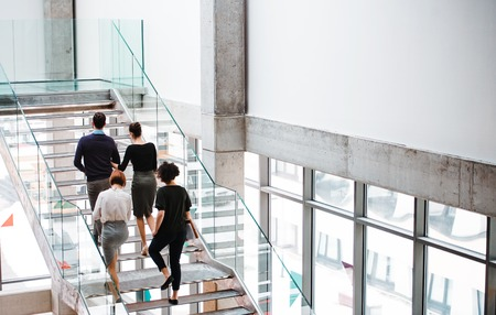 Foto de Rear view of group of young businesspeople walking up the stairs. - Imagen libre de derechos