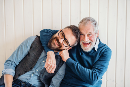 Photo for A portrait of adult hipster son and senior father sitting on floor indoors at home. - Royalty Free Image