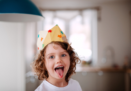 Photo pour A small girl with a paper crown at home, having fun when looking at camera. - image libre de droit
