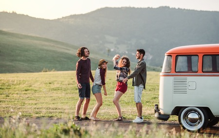 Photo pour A group of friends standing outdoors on a roadtrip through countryside, dancing. - image libre de droit