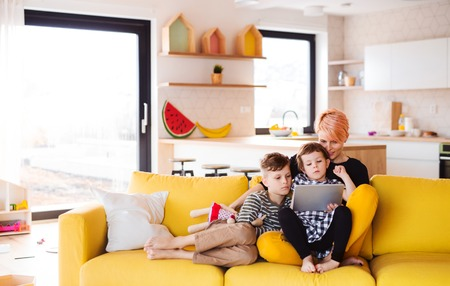 Photo for A young woman with two children indoors at home, using tablet. - Royalty Free Image