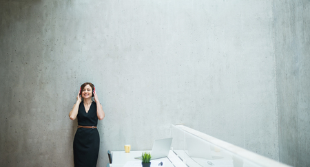 Photo pour Young business woman with headphones standing against concrete wall in office. - image libre de droit