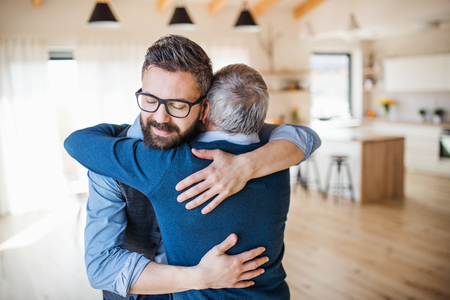 Photo for An adult son and senior father indoors at home, hugging. - Royalty Free Image
