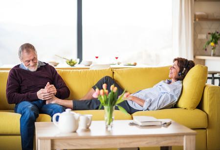 Foto de Affectionate senior couple in love sitting on sofa indoors at home, relaxing. - Imagen libre de derechos